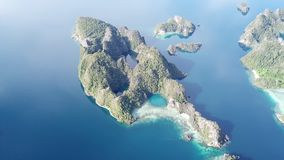Aerial Footage of Scenic Islands in Raja Ampat. The scenic limestone islands in Misool, Raja Ampat are surrounded by healthy, shallow coral reefs. This remote stock footage