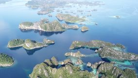 Aerial Footage of Scenic Rock Islands in Raja Ampat. The scenic limestone islands near Misool, Raja Ampat, are surrounded by healthy, shallow coral reefs. This stock footage