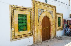 The tiled facade of medieval edifice, Sfax, Tunisia. The scenic mansion`s facade with traditional horseshoe Arabic gate and windows, decorated with floral tiled Stock Image
