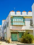 The scenic mansions of Kairouan, Tunisia. KAIROUAN, TUNISIA - AUGUST 30, 2015: The scenic white mansion with colored doors and balconies, decorated with fine Royalty Free Stock Photo