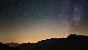 Scenic meteor explosion with stardust during time lapse of the Milky Way and the starry sky rotating over the Alps.