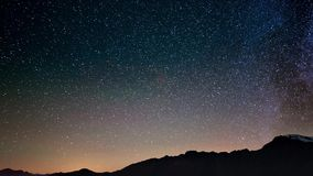 Scenic meteor explosion with stardust during time lapse of the Milky Way and the starry sky rotating over the Alps stock footage