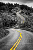Scenic monochrome view of narrow curvy road and rural landscape Royalty Free Stock Image