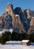 Scenic mountain cabin. Small wooden mountain cabin with a very impressive rock formation in the background. Taken in the vicinity of the village of Corvara in royalty free stock image