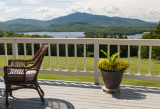 Scenic mountain house deck. House with outdoor deck and pretty potted flower overlooking a scenic lake and mountain.  Moosehead Lake, Greenville, Maine Royalty Free Stock Photography
