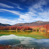 Scenic mountain lake with autumnal forest along the shore and bl Royalty Free Stock Photography
