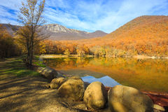 Scenic mountain lake with autumnal forest and big stones along t Royalty Free Stock Images