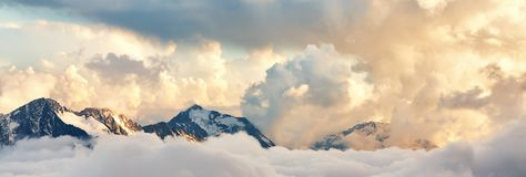 Scenic mountain landscape. Scenic alpine landscape with peaks covered by snow and clouds. natural mountain background royalty free stock images