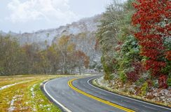 Scenic Mountain Road. A curve in the road with autumn colors and a light dusting of snow stock images