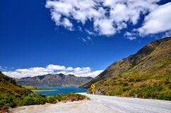Scenic Mountain Road New Zealand. Scenic mountain road in new zealand with Lake Hawea in the background Stock Photo