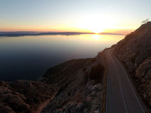 Scenic mountain road with sea view at sunset Stock Images