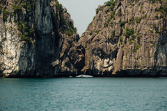 Scenic mountain rock face cliff in the sea water, green trees, a. Sia ha long bay vietnam stock photo