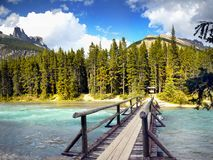 Canadian Rockies Trail, Glacial River Bridge, Banff NP. Scenic mountains, forest and bridge across the glacial river in Canadian Rockies. Canadian landscape stock photo