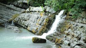 Scenic nature of a beautiful waterfall and emerald of a fresh water lake in a wild jungle forest environment. 4k, slow