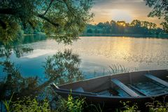 Scenic nature landscape near lake. Rowing boat in summer morning Stock Photos
