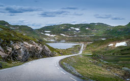 Scenic Norwegian road throgh the lakes and rocks with some snow. Scenic mountain road through the rocks and lakes with some snow on the green hills. Norway Stock Images