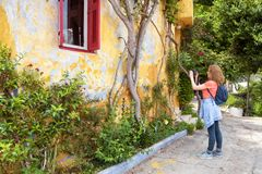 Scenic old street with overgrown house in Plaka district, Athens. Greece. Plaka is one of the main tourist attractions of Athens. Young woman traveler takes a royalty free stock photos