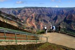 Scenic Overlook Waimea Canyon. Four tourists look out over Waimea Canyon on Kauai, Hawaii.  Deep ravines and rocky crags.  Blue skies and small clouds Royalty Free Stock Photography