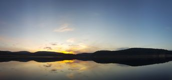 Scenic panorama view of sunset under a cloudy sky panorama with sun reflection over water. Beautiful scene of a lake while golden sunset / sunrise – sun royalty free stock photos
