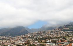 Panoramic aerial cityscape of the city of funchal in Madeira with buildings of the city in front of mountains with the royalty free stock photo
