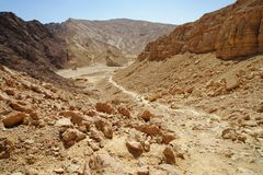 Scenic path descending into the desert valley, Israel. Scenic path descending into the desert valley, Shekhoret canyon near Eilat, Israel Stock Photo