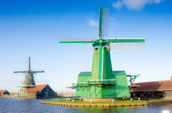 Scenic picture of the water and windmills in Zaanse Schans, Holland, Europe against the backdrop of a cloudy sky. royalty free stock photos