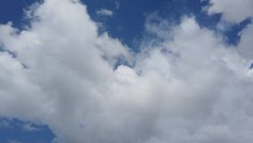 Scenic puffy cumulus clouds flies fast and carefree in a blue summer sky.  stock footage