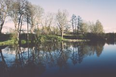 Scenic reflections of trees and clouds in water - retro vintage Stock Photo