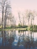 Scenic reflections of trees and clouds in water - retro vintage Stock Images