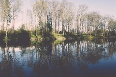 Scenic reflections of trees and clouds in water - retro vintage Stock Photos