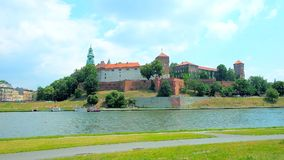 In riverside park of Krakow, Poland. The scenic riverside park with a view on medieval Wawel Castle across the Vistula river, Krakow, Poland stock video footage