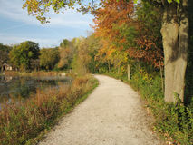 Scenic road. Gravel path lined with fall colred trees Stock Image