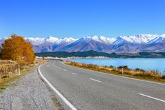 Scenic Road along Lake Tekapo at beautiful sunny morning . Lake Tekapo and mountains with snow in autumn, Canterbury, South Is Royalty Free Stock Photography