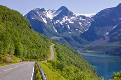 Scenic road by fjord. Coastal road in Norway leading to Bodo with snowy mountains of Saltfjellet-Svartisen National Park in the background Stock Images