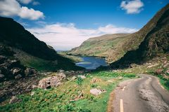 The scenic road of Gap of Dunloe, a narrow mountain pass in county Kerry, with Augher lake in the background. The scenic road of Gap of Dunloe, a narrow mountain stock photo