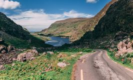 The scenic road of Gap of Dunloe, a narrow mountain pass in county Kerry, with Augher lake in the background. The scenic road of Gap of Dunloe, a narrow mountain stock images