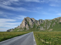 Scenic road and mountains in Norway. Straight scenic road and beautiful mountains. Summer Norwegian landscape Royalty Free Stock Photography