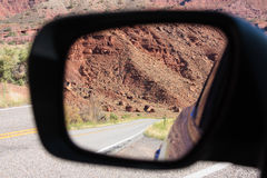 Scenic road reflected in mirror. A scenic road reflected in the side view mirror of a car Royalty Free Stock Photos