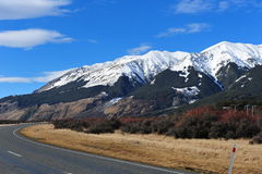 Scenic road with snow mountains Royalty Free Stock Photo