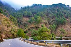 Scenic road through the valley of banikhet dalhousie himachal pradesh covered with mountain and trees. Driving uphill scenic road. Travel concept stock image