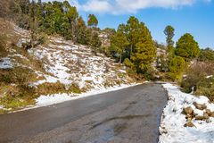 Scenic road through the valley of banikhet dalhousie himachal pradesh covered with Snow mountain and trees. Driving uphill scenic. Road winter travel concept stock photography