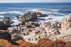 A scenic rocky beach through Pebble Beach and Pacific Grove on the Monterey Peninsula in California. Tilt-shift photography for blurry and miniature effect stock photography