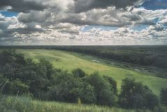 Scenic Russian Landscape. Meadows, river and hills under a cloudy sky.  Royalty Free Stock Photo