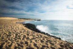 Scenic sandy beach on atlantic coastline with breaking waves in blue sky Stock Image