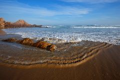 Scenic sandy beach  with waves and blue sky Stock Photos