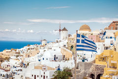 Scenic Santorini with Greek flag. Top of white church and bells, Greek flag with blue sea at Oia, Santorini, Greece stock photo