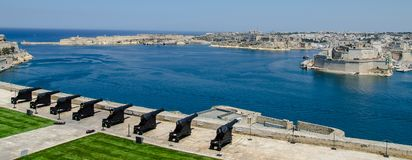 Cannons Guarding the Harbor. A scenic seascape of the harbor in Valetta, Malta with the cannons of the fort in the foreground Stock Photos