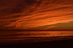Scenic seascape with a sunset with warm orange colors in the sky. Warm colors all over the sky during a sunset in california Royalty Free Stock Photos