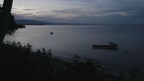 Scenic shot of boats after sunset. A scenic still shot of two small boats floating in the lake stock video footage