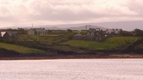 Scenic shot of houses. A scenic shot across a river of houses sitting on a beautiful green landscape stock video footage